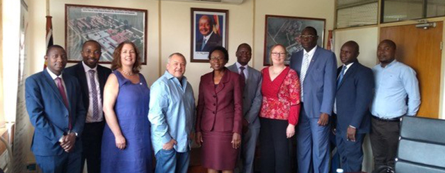 Minister of health Dr Jane Aceng (centre) with CRUK Cambridge Institute Director Greg Hannon (4th from left) and Suzanne Turner (4th from right) at the Ministry of Health, Kampala, Uganda.